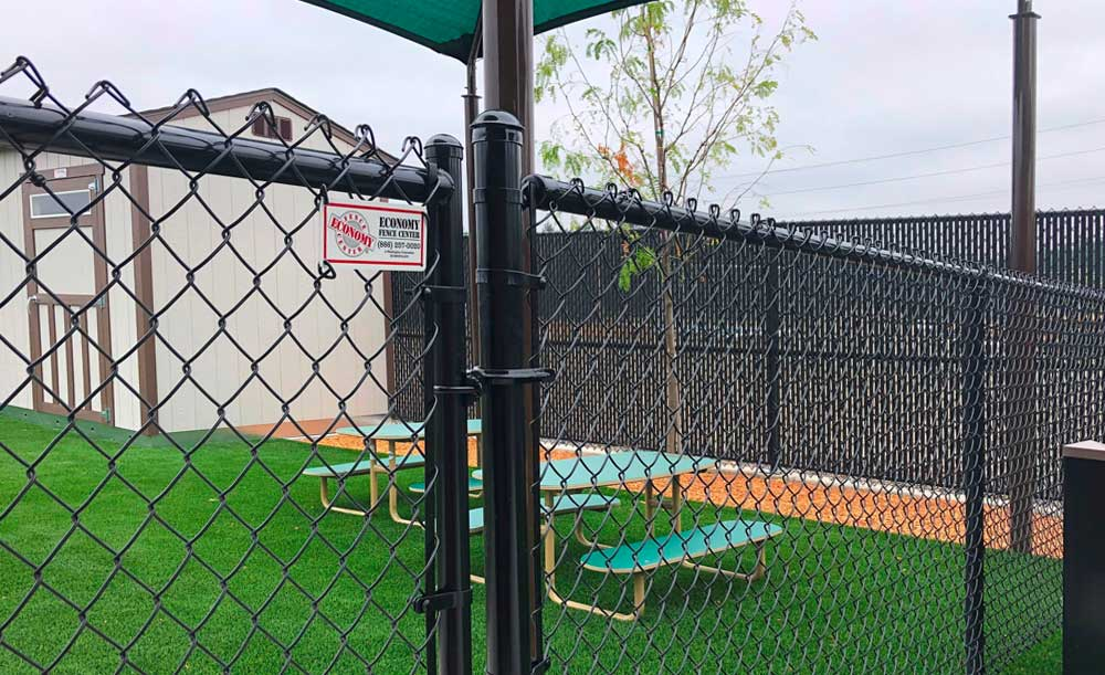 Black chain link fence, single-swing gate and privacy slats