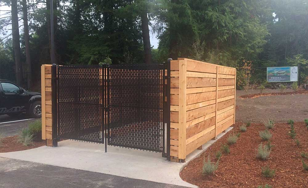 Dumpster Enclosure with black chain link gates with black privacy slats