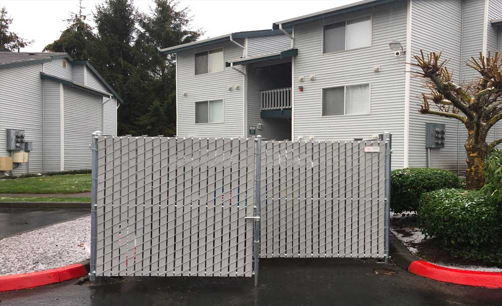Dumpster enclosure with gray privacy slats