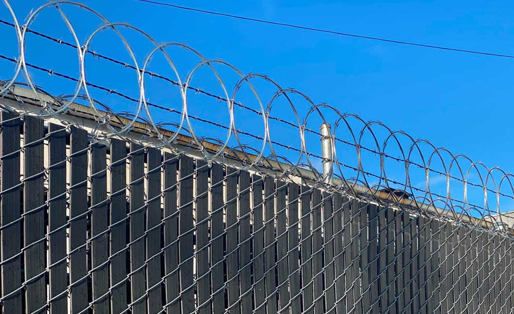 Security fence with privacy slats, barb-wire and razor ribbon