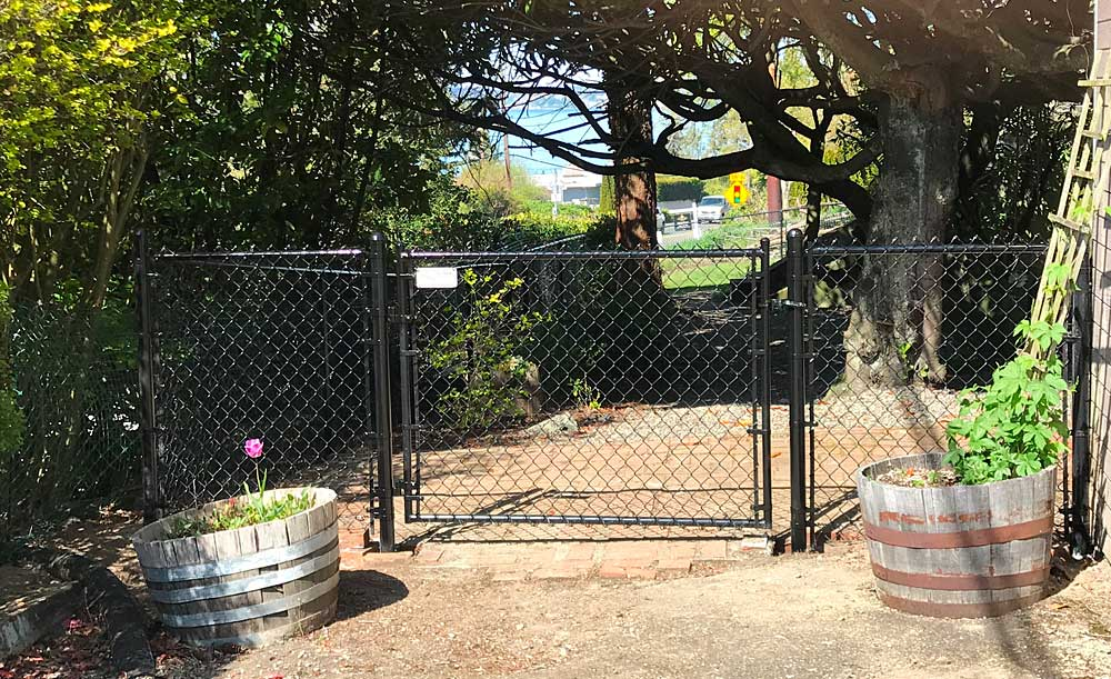 Black chain link fence with single-swing gate