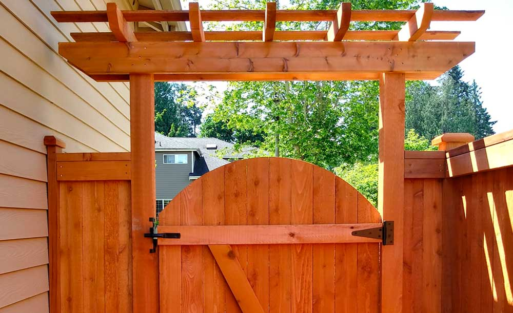 Modified Panel style pre-stained cedar fence with pipe-base posts and crown top gate with trellis (backside)