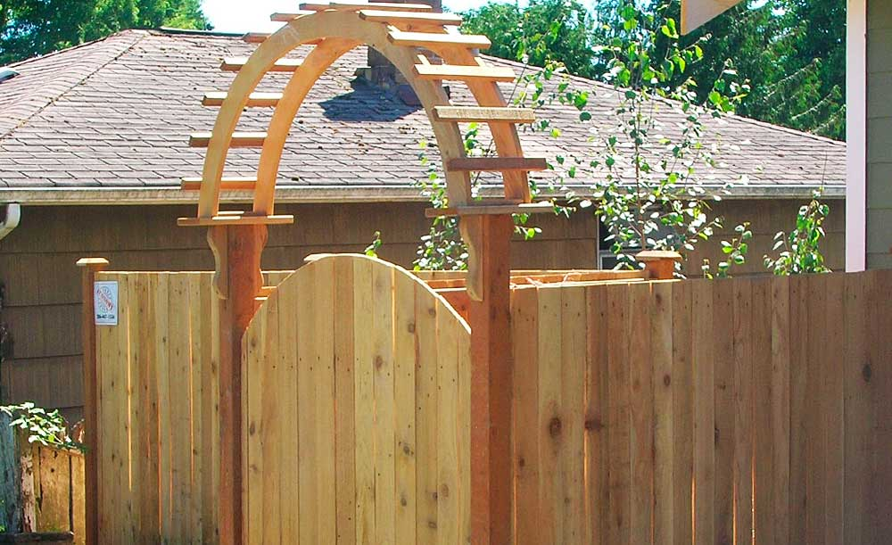 Estate style cedar fence with crown top gate and gateway arbor