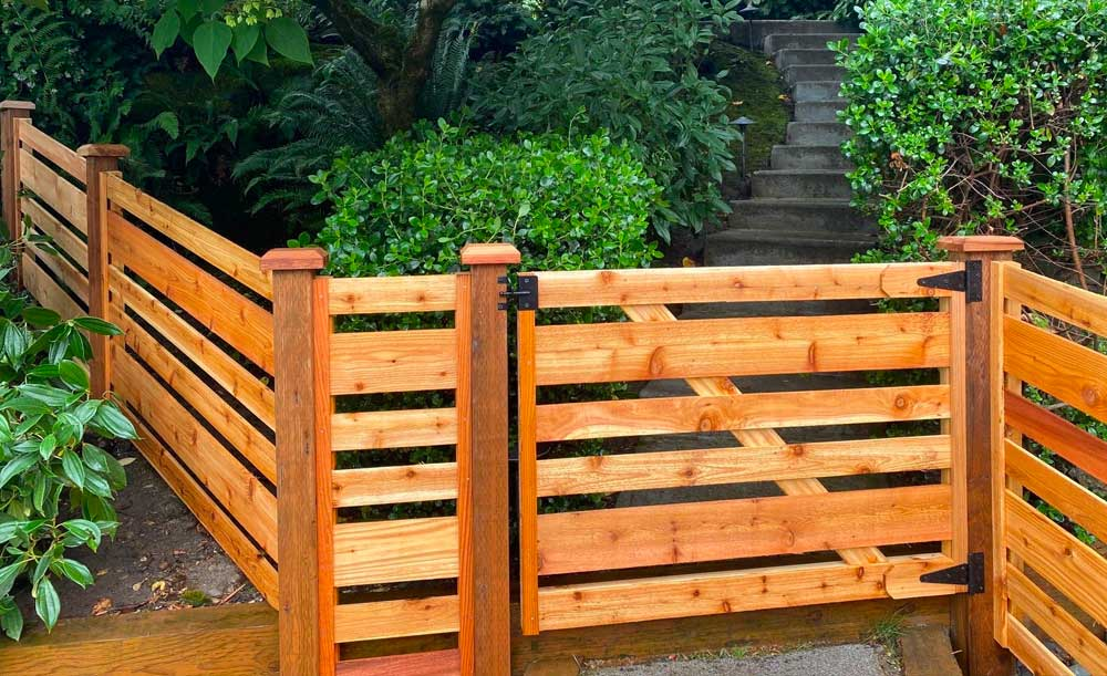 Horizontal cedar fence with space, alternating boards and gate