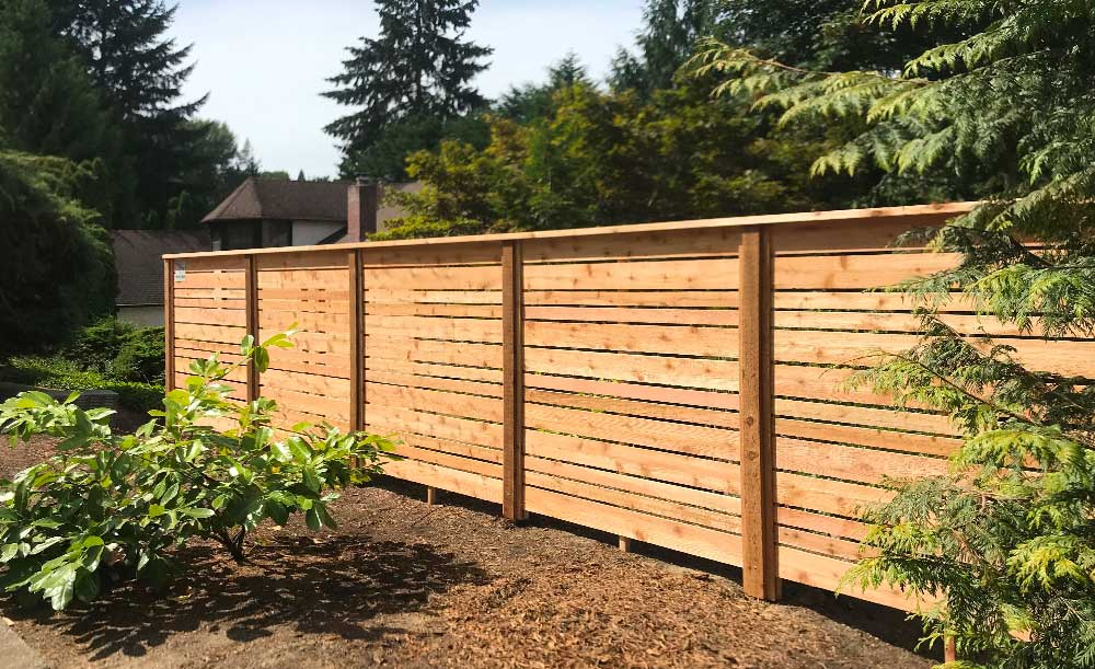 Horizonal style cedar fence with space and alternating boards