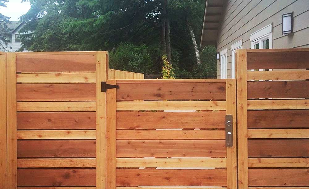 Horizontal style cedar fence with space and alternating boards