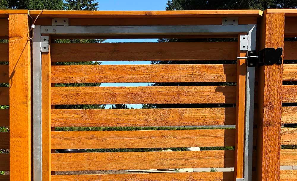 Horizontal pre-stained cedar fence with pipe-base posts and steel framed gate