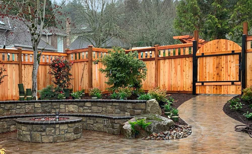 Lexington style cedar fence with black steel-frame gate and trellis behind